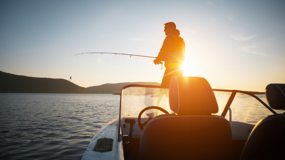 man fishing on bow of boat